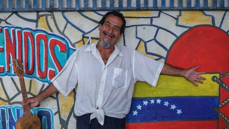 O artista Ramos mostra com alegria um dos murais que pintou no abrigo Tancredo Neves, em Boa Vista (RR).
