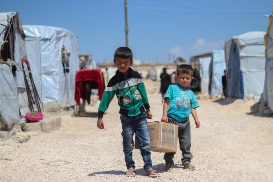 Os irmãos sírgios Ahmad, 7 anos, e Saad, 5, carregam kit de higiene familiar no acampamento Fafin, zona rural do norte de Alepo