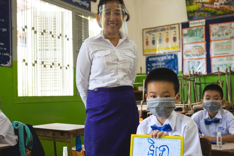 Professora e alunos usam máscaras e fazem distanciamento físico em escola primária em Phnom Penh, no Camboja.