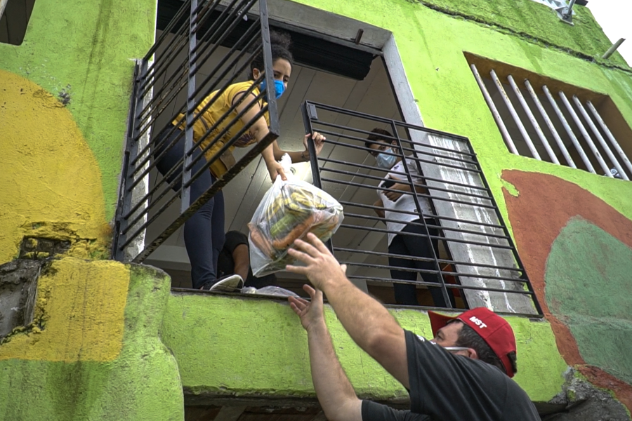 De dentro do barco, Paulo Manfan distribui alimentos
